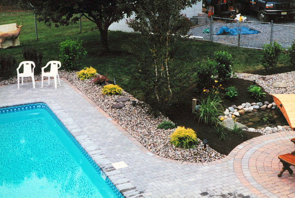 Modern pool landscaping ideas with rocks and plants for Garden near pool
